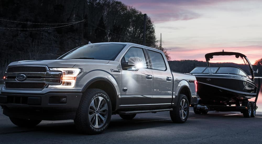 A white 2020 Ford F-150 King Ranch, which is a popular trim option among used Ford trucks, is towing a boat out of a lake near Albany, NY.