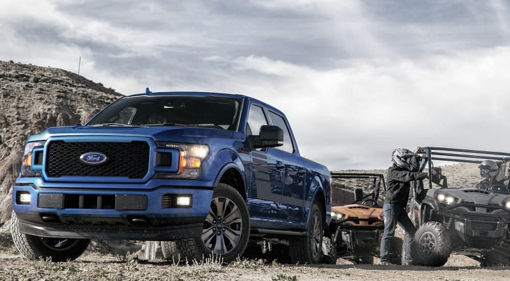 A blue 2020 Ford F-150 XLT is parked on a dirt path next to side-by-sides.