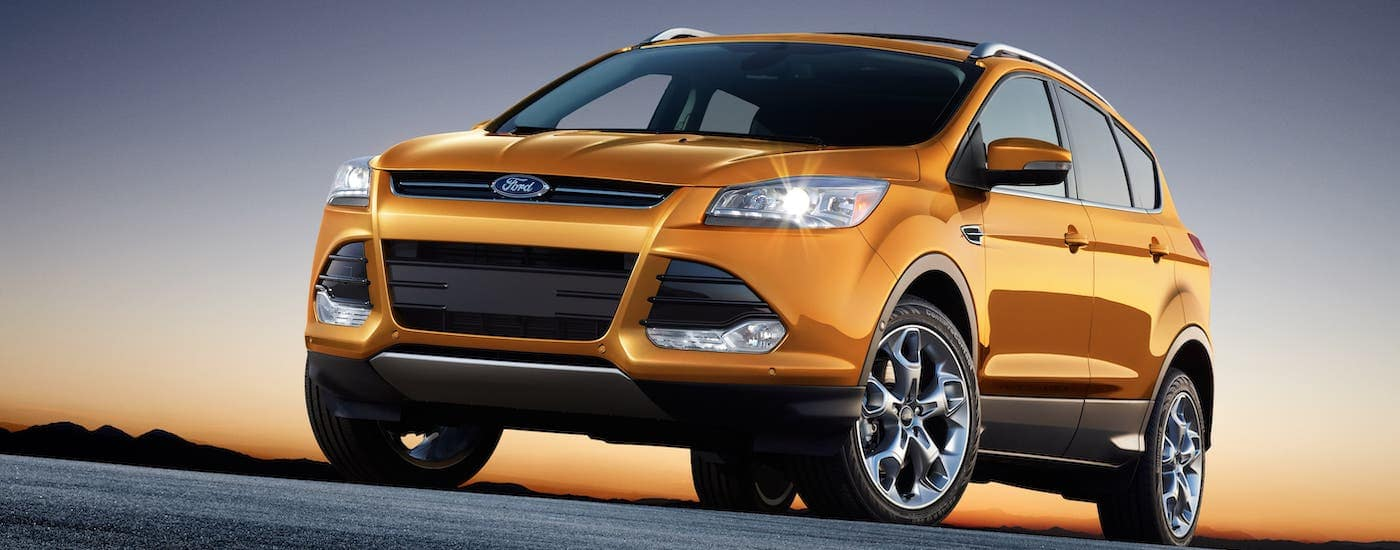 An orange 2016 Ford Escape is parked against a purple and orange sunset, find Used SUVs for Sale in Albany NY.