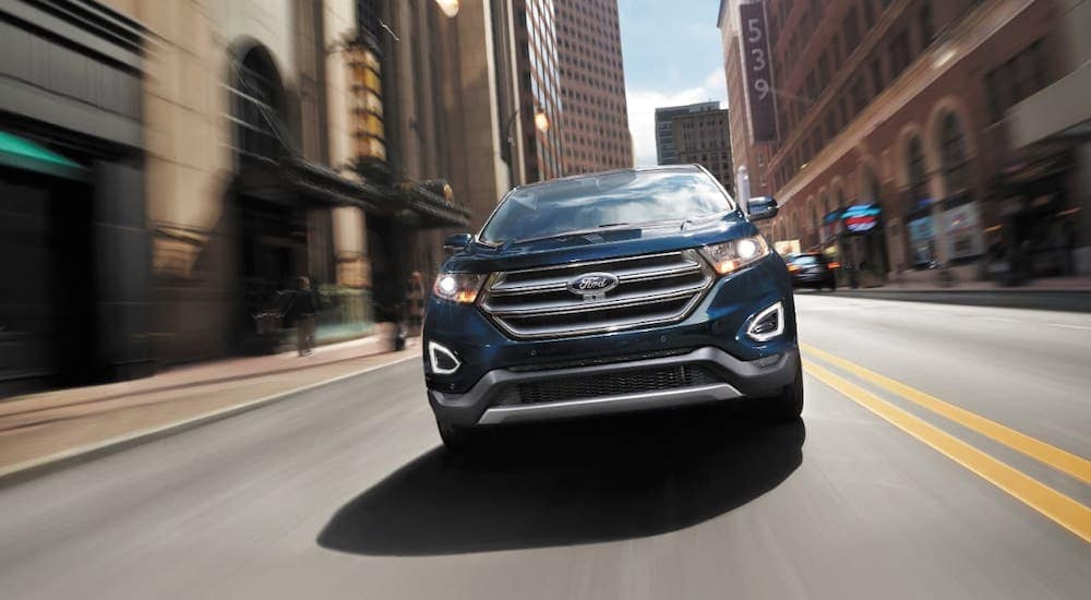 A blue 2017 Ford Edge is racing through a city street near Albany, shown from the front.