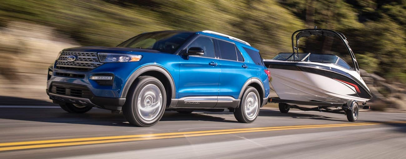 A blue 2020 Ford Explorer, which wins when comparing the 2020 Ford Explorer vs 2020 Jeep Grand Cherokee, is towing a boat past trees outside of Cincinnati, OH.