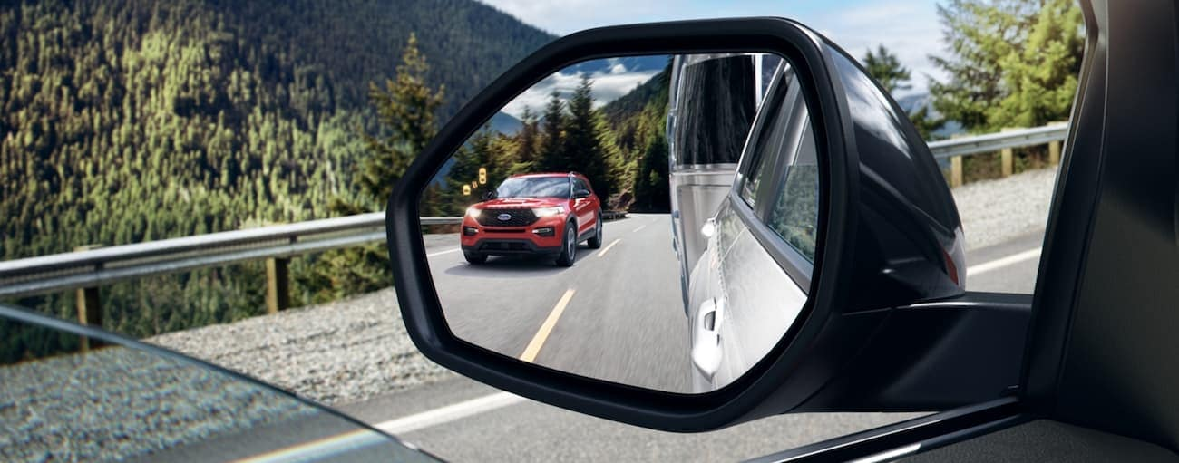 The blind-spot warning in the mirror of a 2020 Ford Explorer is shown with a red Explorer.