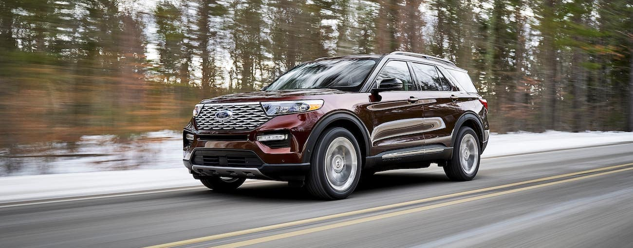 A maroon 2020 Ford Explorer is driving away with a win from 2020 Ford Explorer vs 2020 Kia Telluride, outside Albany, NY.