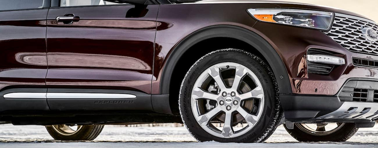 A closeup of a wheel on a maroon 2020 Ford Explorer that is parked in snow outside of Albany, NY.