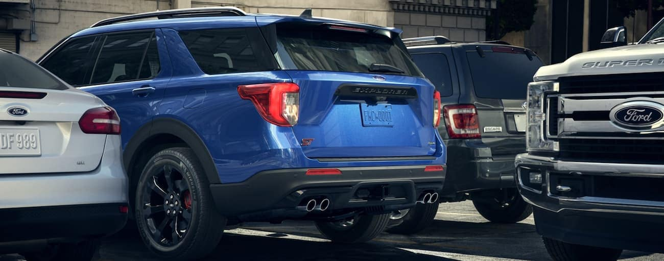 A blue 2020 Ford Explorer is reversing out of a parking spot as a Ford truck drives by.