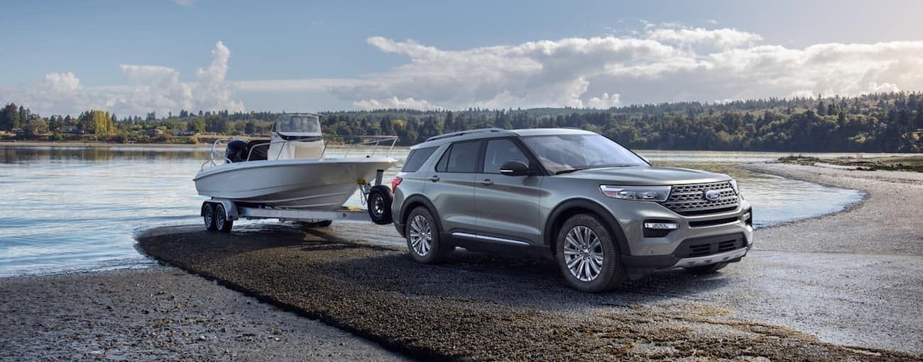A silver 2020 Ford Explorer, which wins when comparing the 2020 Ford Explorer vs 2020 Mazda CX-9, is towing a boat out of a lake near Albany, NY.