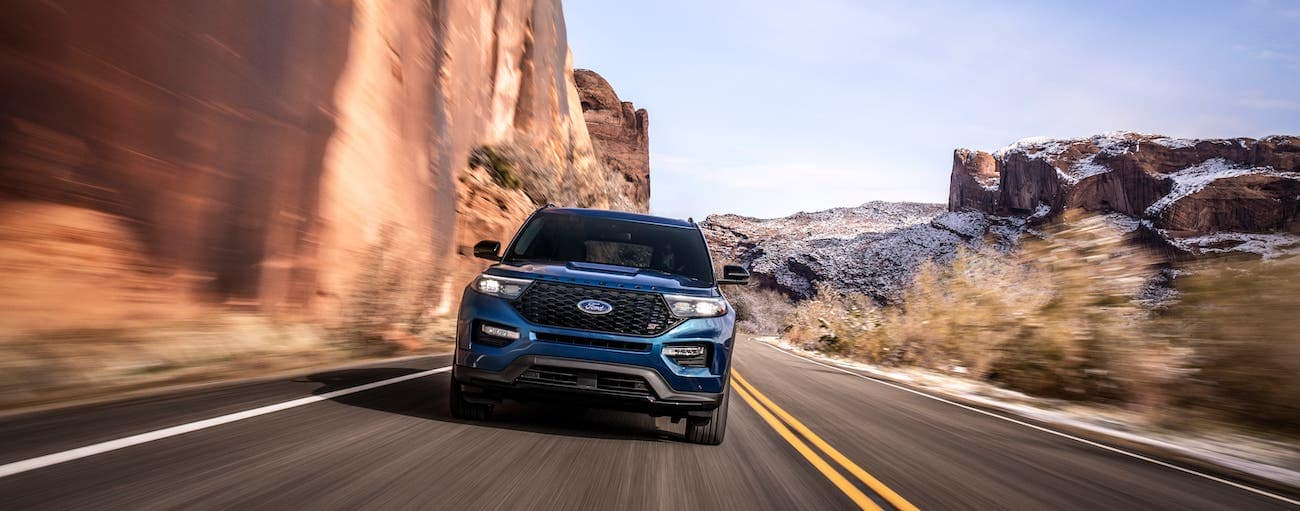 A blue Explorer from the front, the winner of 2020 Ford Explorer vs 2020 Toyota Highlander, is driving on a desert highway.