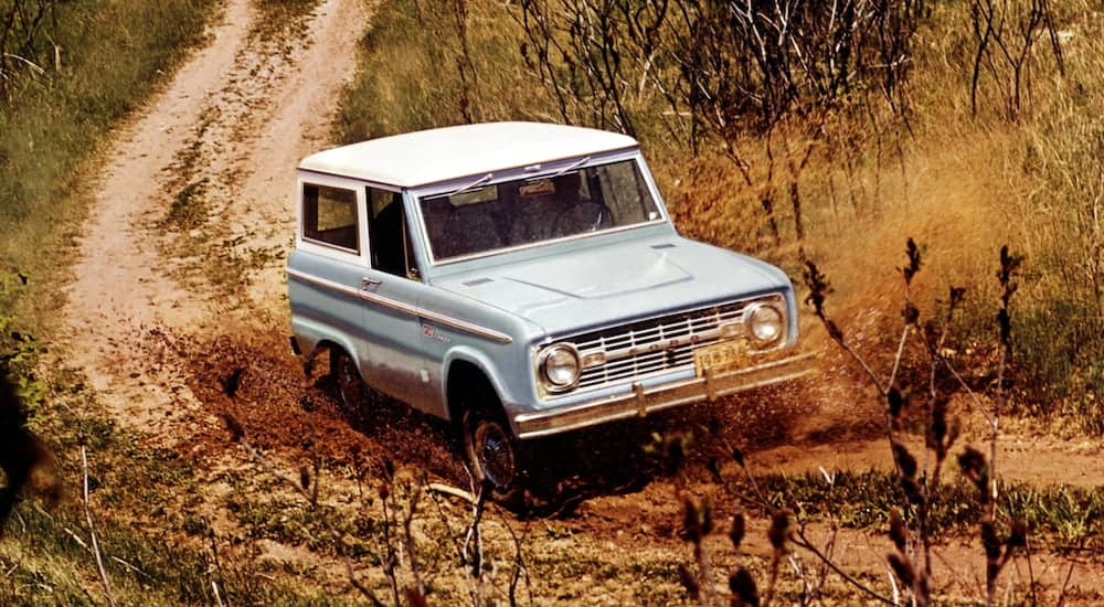 A blue and white 1967 Ford Bronco is off-roading in the mud near Albany, NY.