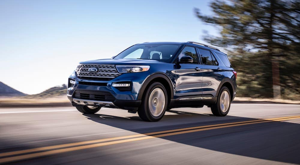One of the popular Ford SUVs, a blue 2020 Ford Explorer Limited, is driving on a highway.