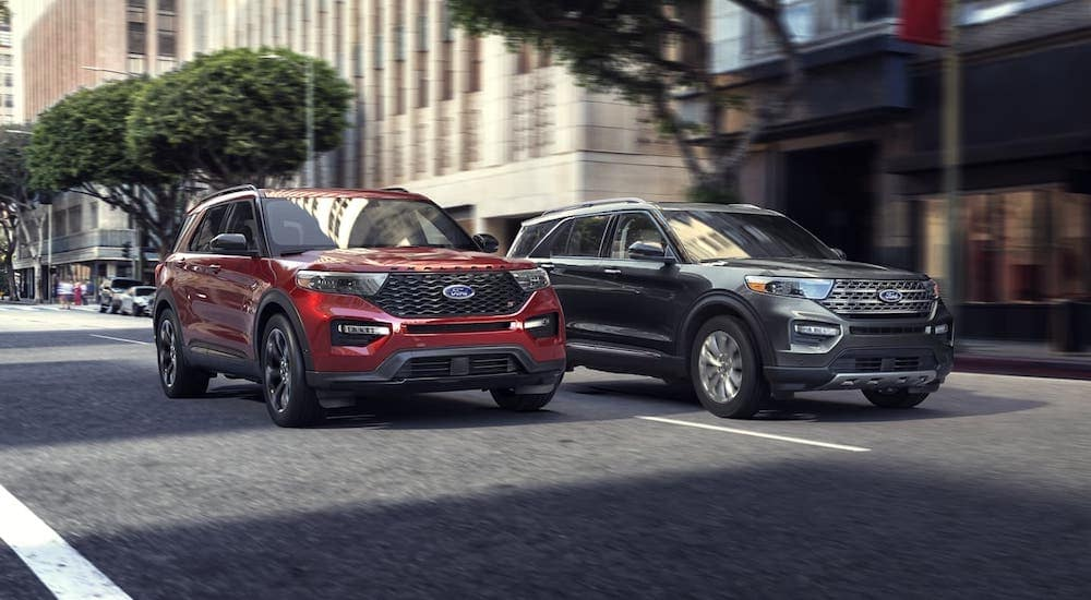 Two popular Ford SUVs, a red and a gray 2020 Ford Explorer on a city street.
