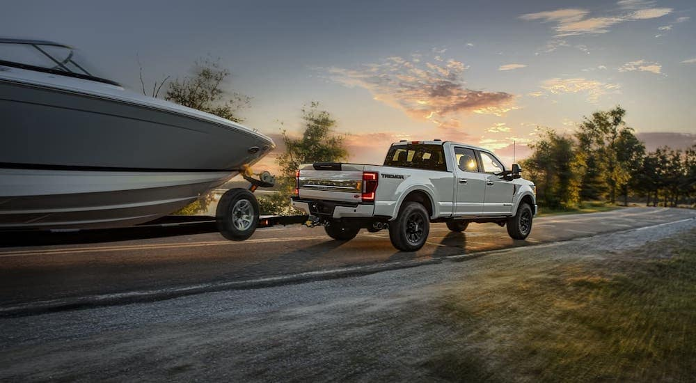 A white 2020 Ford Super Duty is towing a boat at dusk outside Albany, NY.