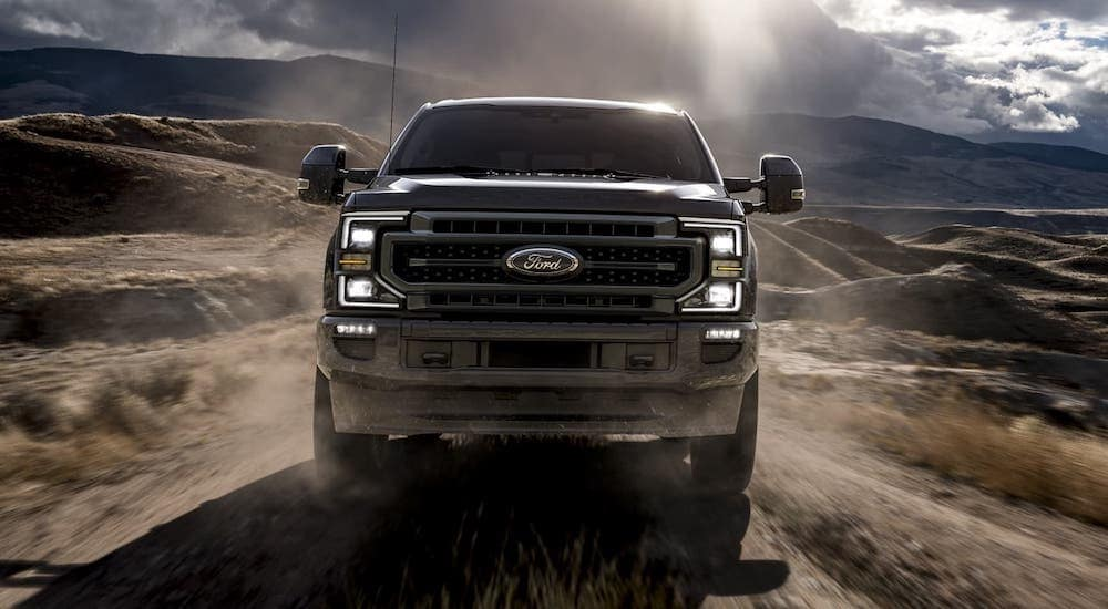 One of the popular Ford Trucks, the front of a 2020 Ford Super Duty is driving in a desert.
