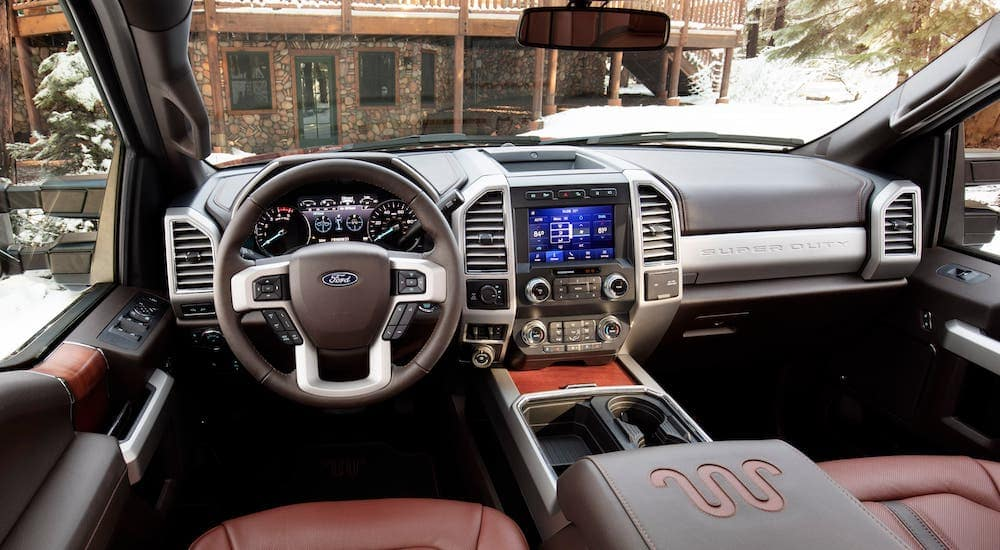 The interior and front seat of a 2020 Ford Super Duty overlooking a winter cabin.