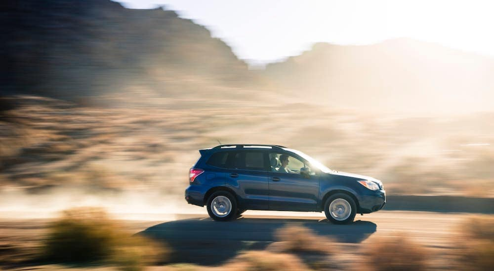 A blue 2014 Subaru Forester is driving on a desert road.