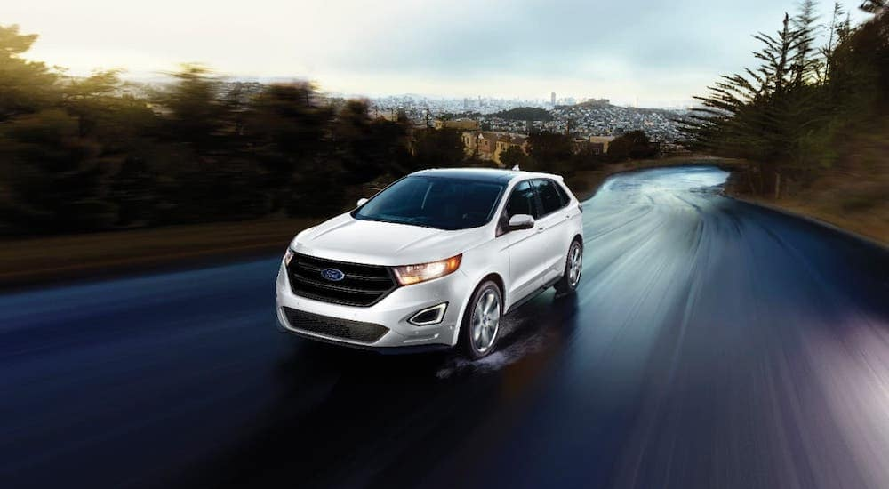 A popular used SUV for sale, a white 2016 Ford Edge, is driving away from a city near Albany, NY.