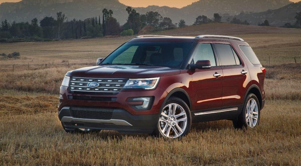 A red 2016 Ford Explorer is parked in a field in front of mountains.