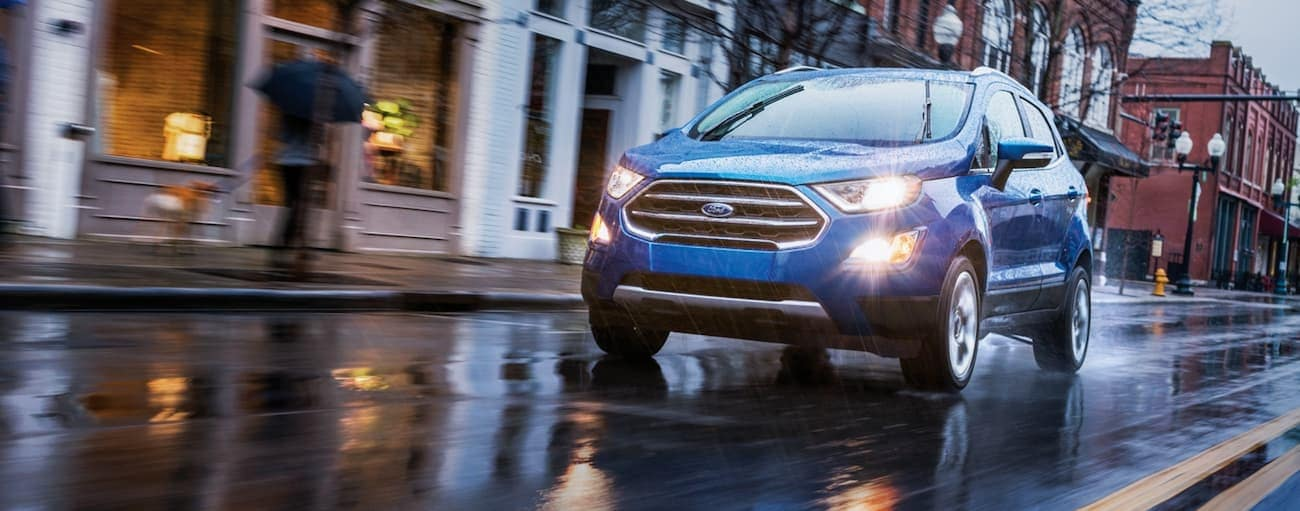 A blue 2020 Ford EcoSport is driving in the rain on a city street near Indiana, PA.