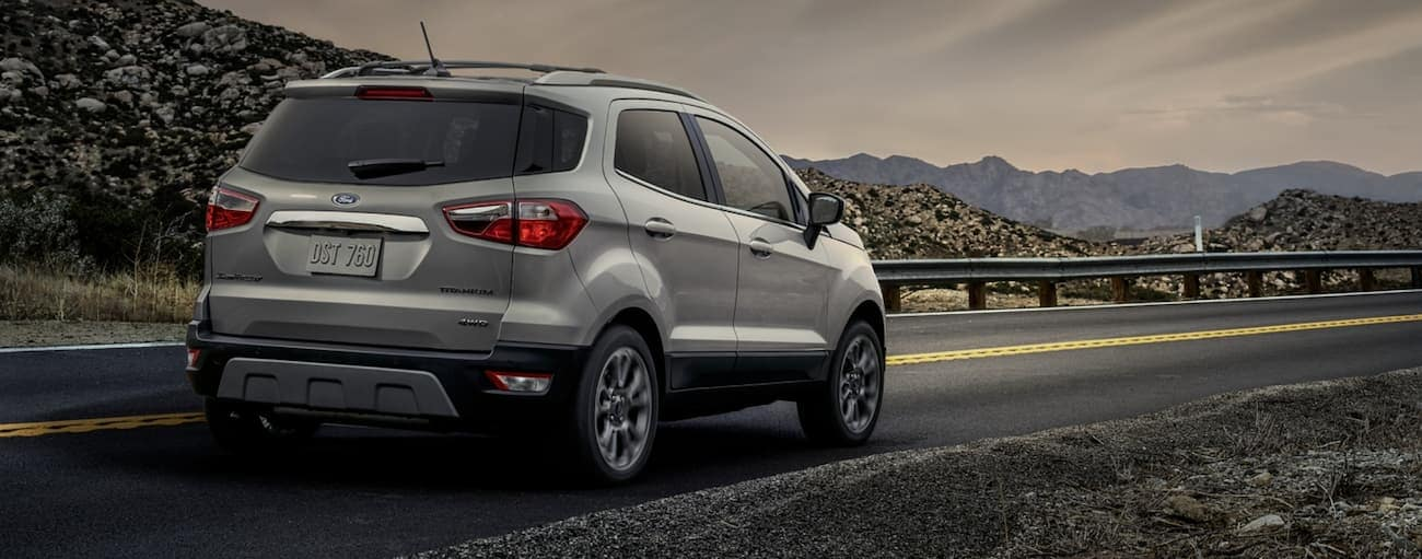 A silver 2020 Ford EcoSport is driving towards distant mountains.