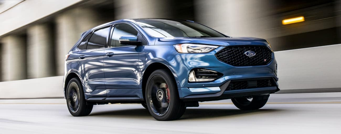 A blue 2020 Ford Edge, which wins when comparing the 2020 Ford Edge vs 2020 Jeep Cherokee, is driving on a blurred highway.