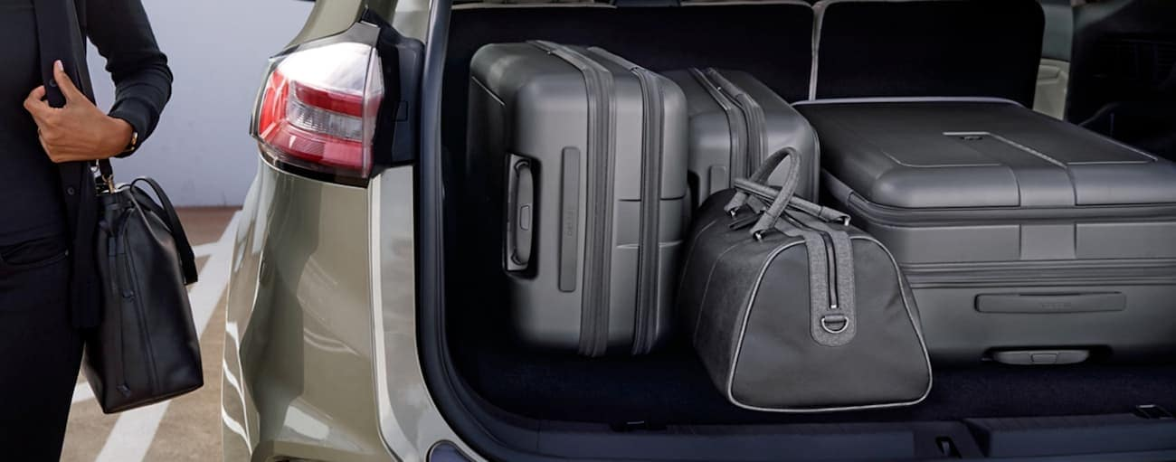A woman is next to the open trunk of her 2020 Ford Edge with luggage inside.