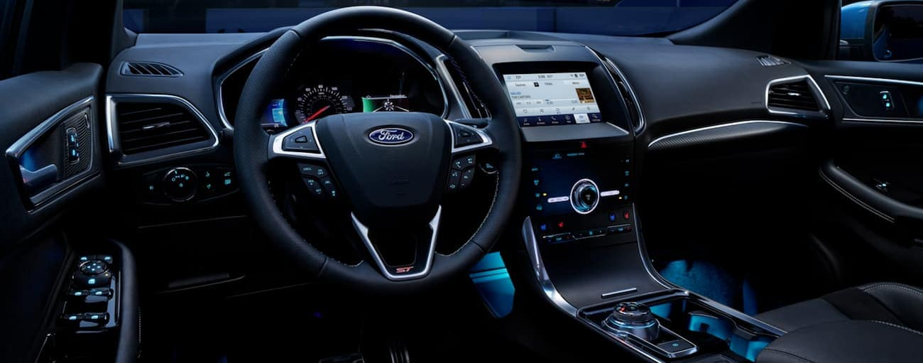 The dashboard of a 2020 Ford Edge is shown lit up at night.