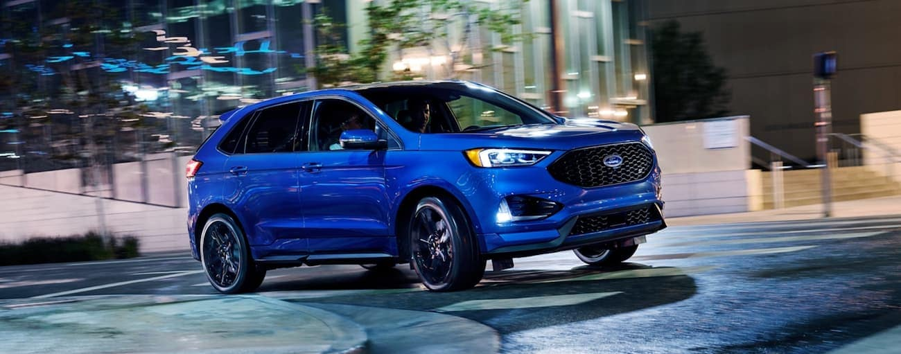 A blue 2020 Ford Edge, which wins when comparing the 2020 Ford Edge vs 2020 Kia Sorento, is turning in an intersection in a city at night.