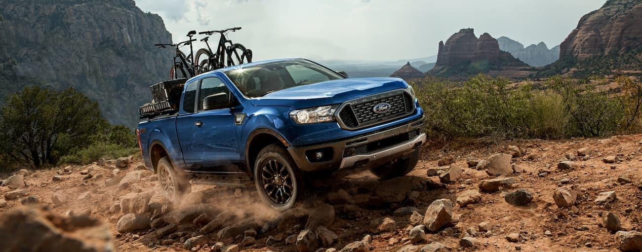 A blue 2020 Ford Ranger with bikes in the bed is off-roading in a mountainous area.