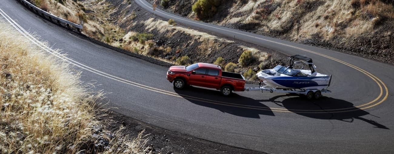 A red 2020 Ford Ranger is towing a boat up a winding road near Albany, NY.
