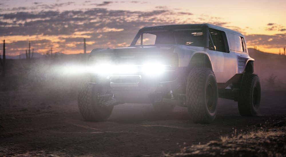 A 2021 Ford Bronco prototype is in the desert at sunset with the headlights shining, which will be popular among Ford SUVs in Albany, NY, after its release.