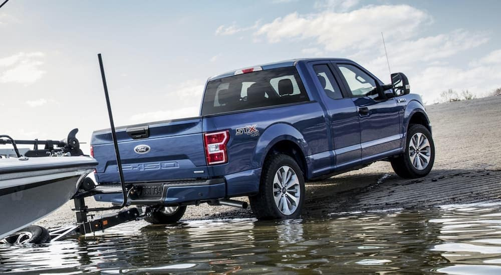 A blue 2020 Ford F-150 is backing a boat into the water.