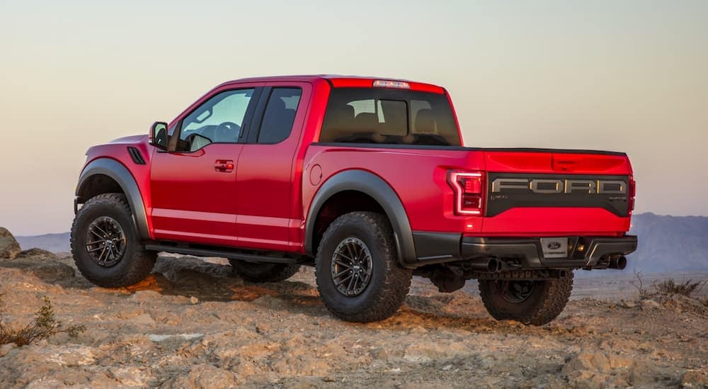 A red 2020 Ford F-150 Raptor is parked with mountain views.
