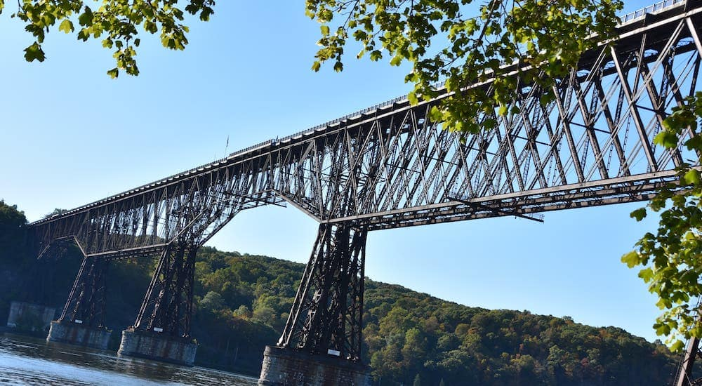 A lower shot of the Poughkeepsie, NY Walkway bridge is against a blue sky.