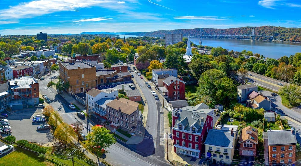 A vibrant aerial shot of the Poughkeepsie, NY skyline is shown.