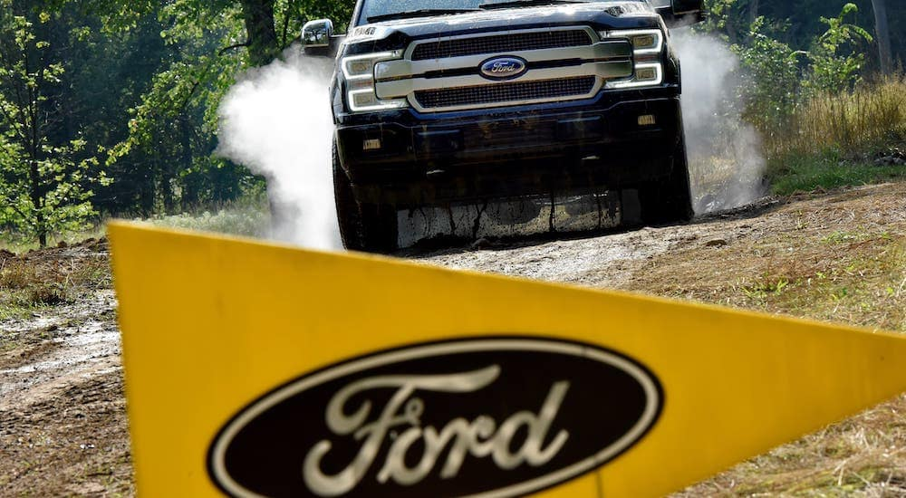 A black 2015 Ford F-150 is off-roading with a yellow Ford flag in the foreground, which is popular among used Ford trucks.