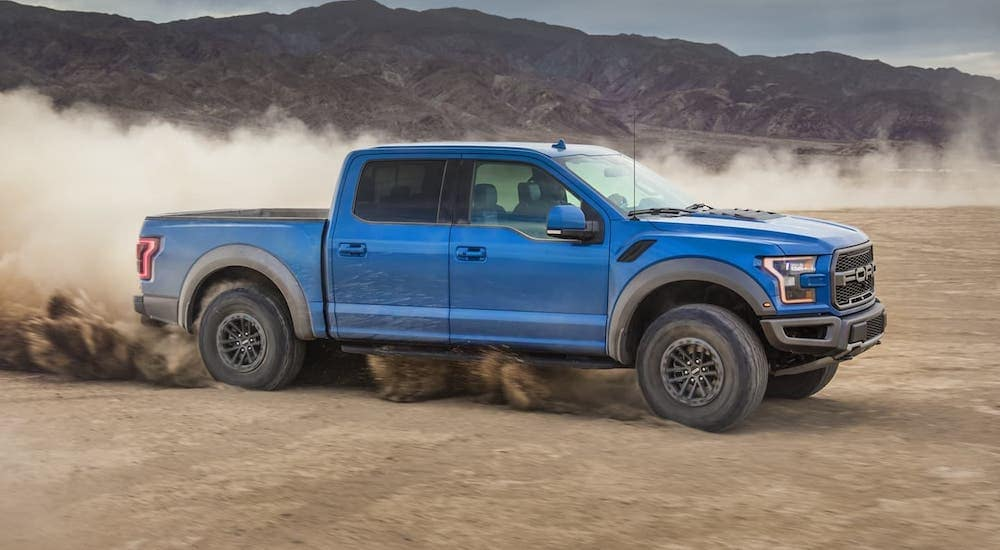 A blue 2020 Ford F-150 Raptor is driving in a desert.