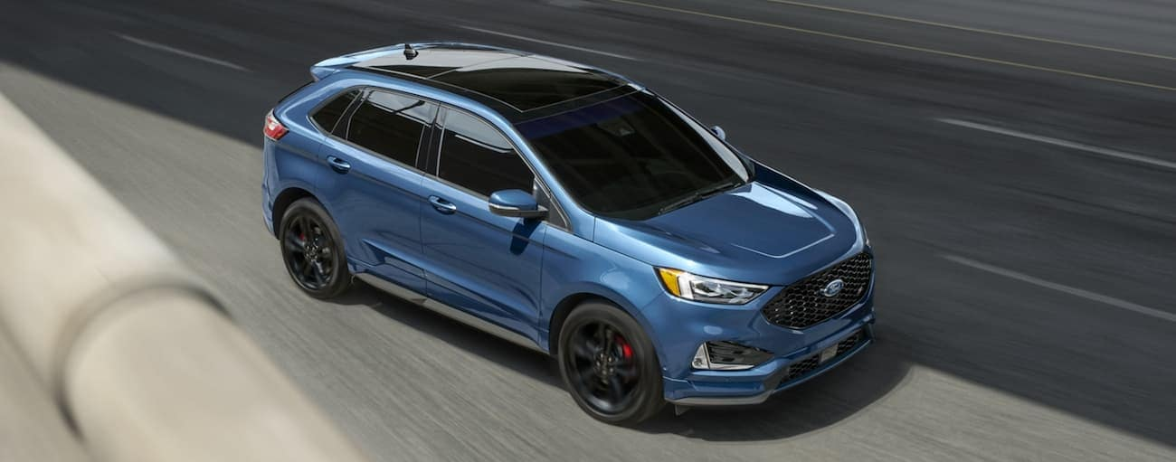 A blue 2020 Ford Edge is shown from above driving on a highway near Albany, NY.