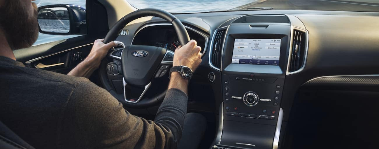 The dashboard and infotainment screen are shown in a 2020 Ford Edge as a man is driving.