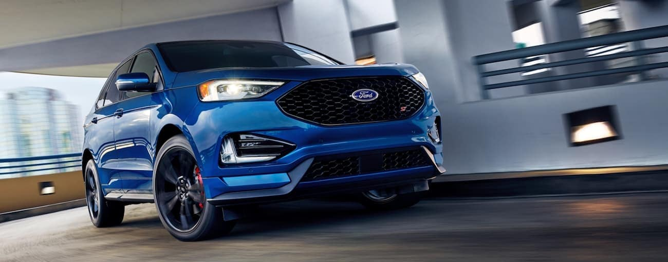 A blue 2020 Ford Edge ST is driving through a parking garage near Albany, NY, after winning the 2020 Ford Edge vs 2020 Dodge Durango comparison.