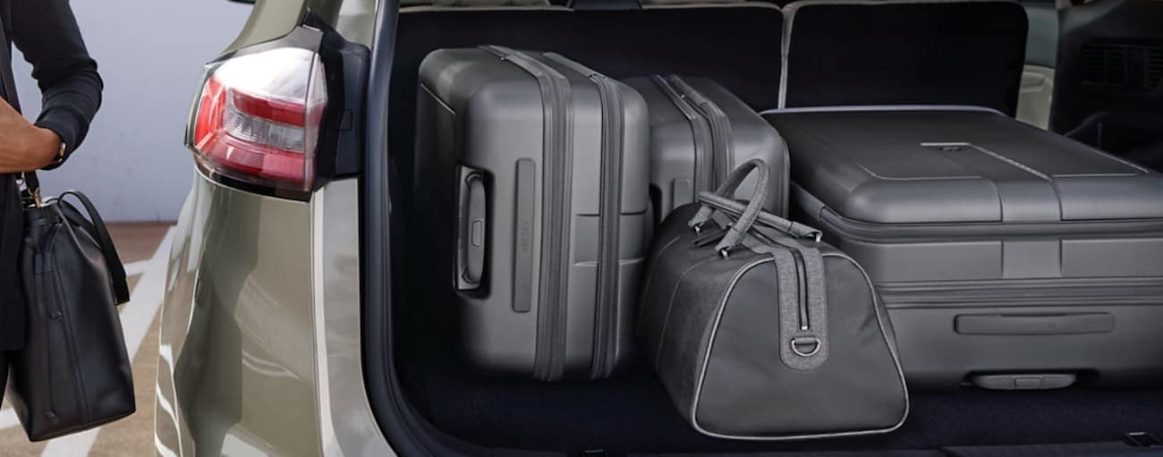 Grey luggage is in the cargo area of a gold 2020 Ford Edge.