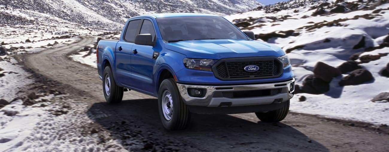 A blue 2020 Ford Ranger is driving on a road through snowy mountains near Albany, NY, after winning the 2020 Ford Ranger vs 2020 Chevy Colorado comparison.