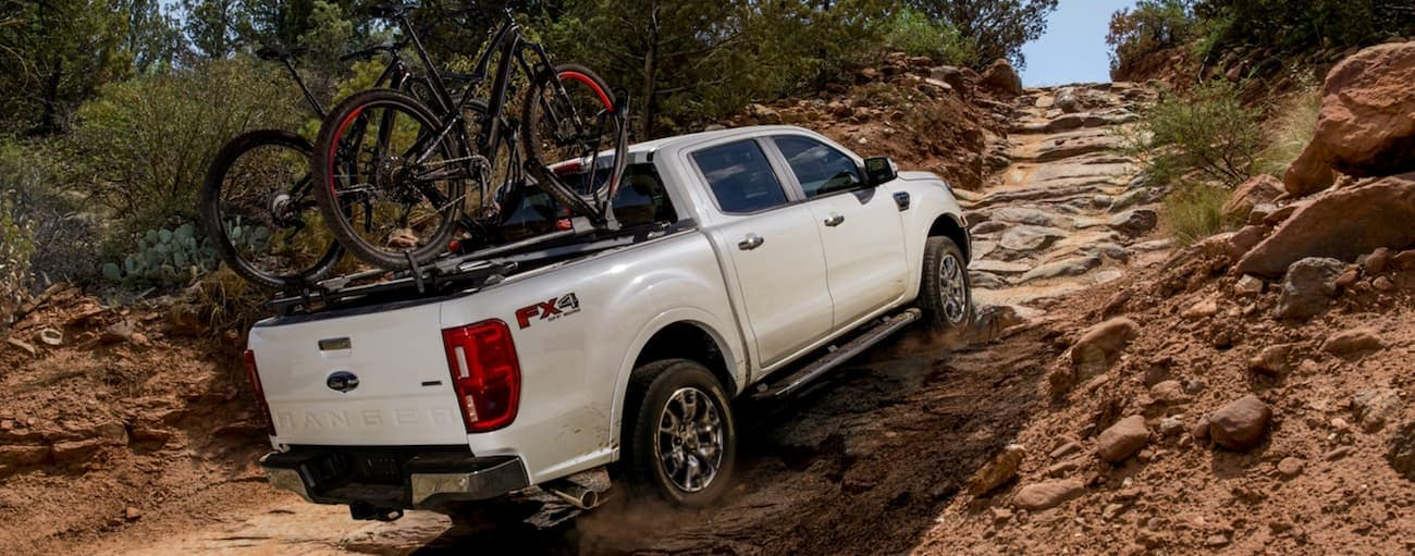 A white 2020 Ford Ranger is off-roading up a rocky trail with bikes on the bed rails.