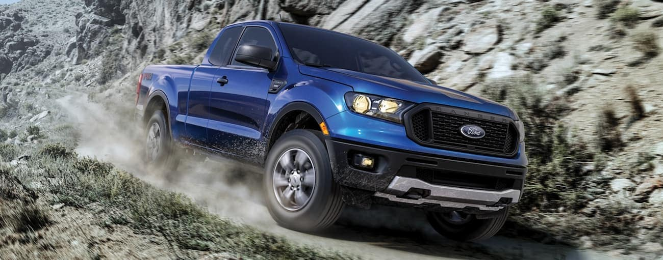 A blue 2020 Ford Ranger is driving on a dirt trail past rock face after winning the 2020 Ford Ranger vs 2020 Toyota Tacoma comparison.