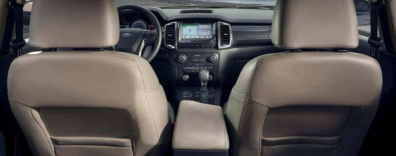 A view of the back of the front seats of a 2020 Ford Ranger with cream interior is shown from the back seat.