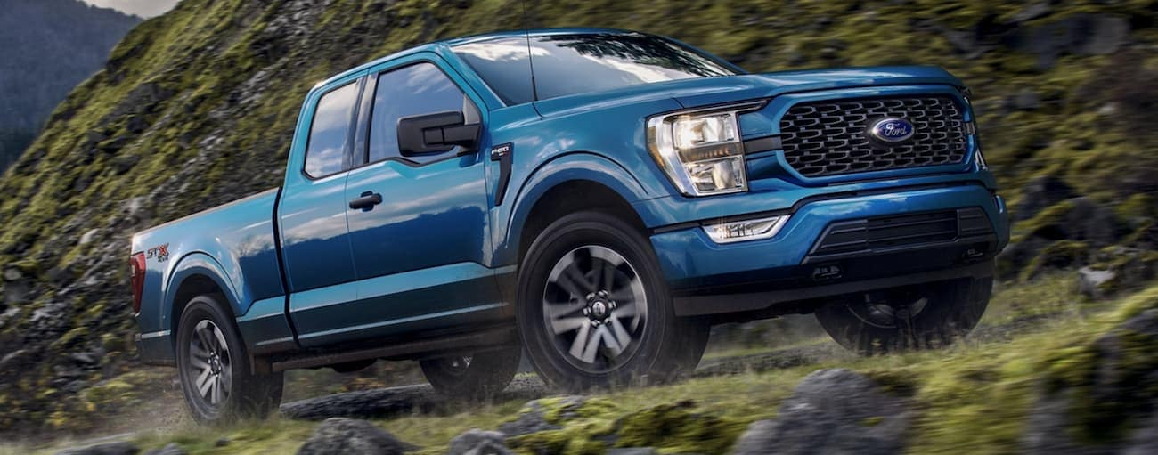 A blue 2021 Ford F-150 is off-roading on a trail in Albany, NY.