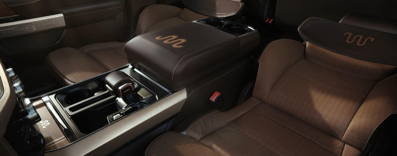 The brown front seats in a 2021 Ford F-150 are in a full recline position.