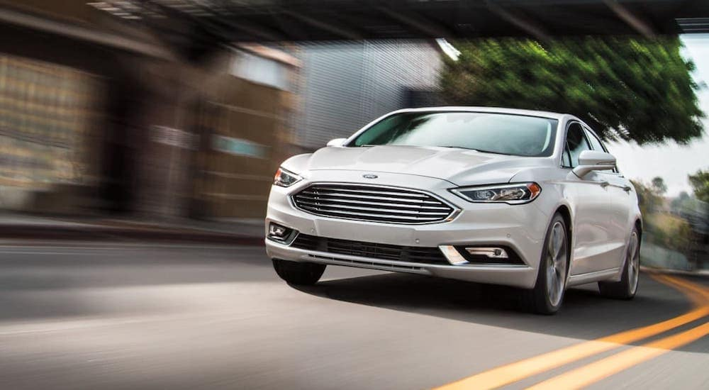 A popular Ford car, a white 2020 Ford Fusion is driving on under a bridge near Albany, NY.