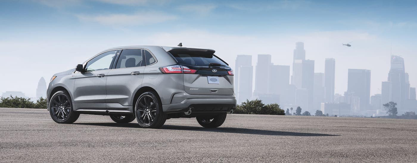 A silver 2020 Ford Edge from a Ford dealership near Troy, NY, is parked in an empty lot with a city skyline in the distance.