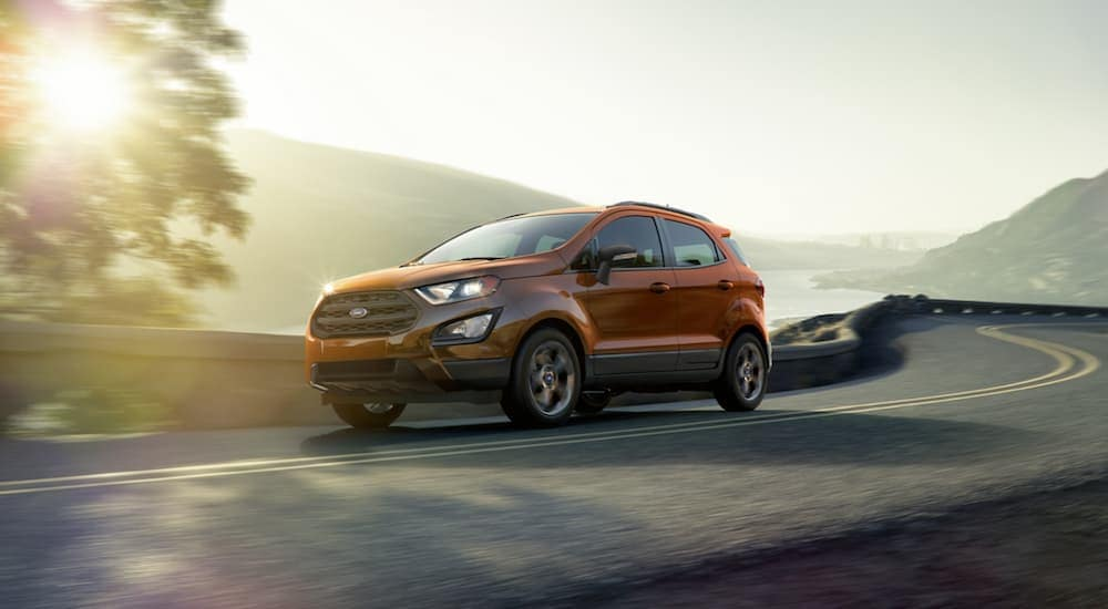 An orange 2020 Ford EcoSport SES, which is popular among Ford SUVs, is driving past hills at sunset near Albany, NY.