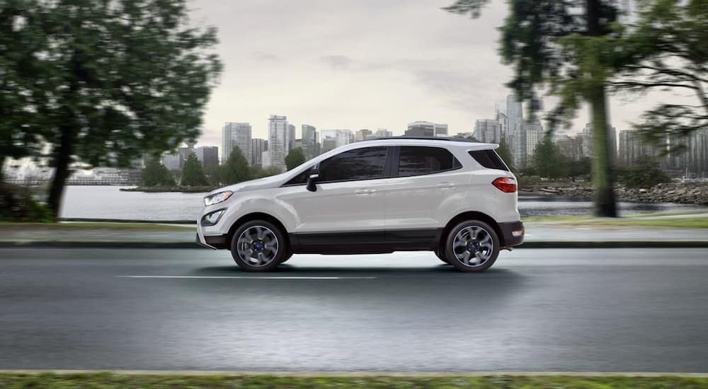 A white 2020 Ford EcoSport is shown from the side driving with a city in the distance.