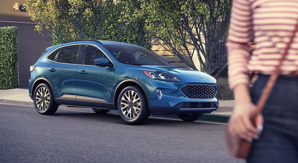 A popular Ford SUV, a blue 2020 Ford Escape S is parked on a street behind a woman in the foreground.